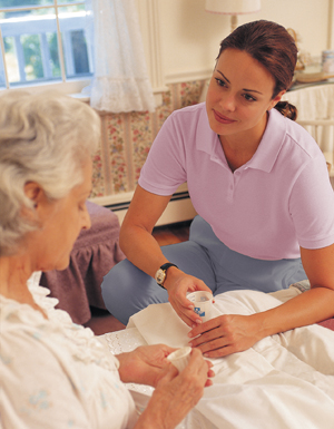 Woman giving medication in cup to older woman in bed.